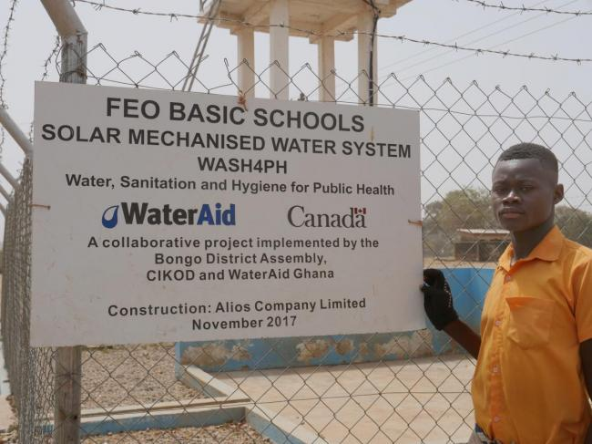 Phileman Azura, aged 15, a student at Foe Junior High School B at the solar mechanised water point installed by WaterAid Ghana and Bongo District Assembly supported by donor money from Canada