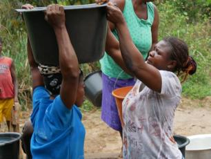 Woman helps other woman lifting her water bucket in Agravi community Ghana