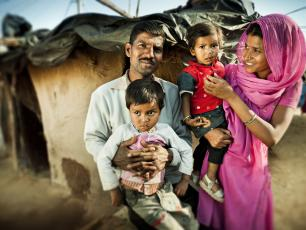 Real people from rural India: Happy parents with their children near their adobe house in slum colony of village.