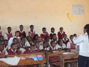 Young girls listening to teacher talking about menstrual hygiene in Kenya