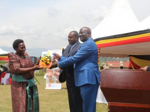 Minister of Local Government (left), receives copies of the district WASH Masterplan from Kabarole District Chairman (right)